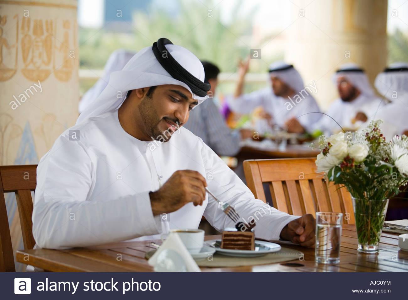 arab-man-eating-dessert-in-cafe-AJC0YM.jpg
